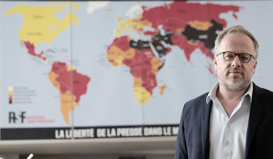 """Christophe Deloire, head of RSF (Reporters without borders) stands in front of the 2021 map of press freedom in Paris, France, Tuesday April, 20, 2021. Reporters Without Borders says there has been a """"dramatic deterioration"""" of press freedom since the pandemic tore across the world. Its new World Press Freedom Index evaluated the media in 180 countries and painted a stark picture. The group says in its annual report that 73% of nations have serious issues with media freedom. It says countries have used the pandemic """"as grounds to block journalists' access to information, sources and reporting in the field."""" The media watchdog says it is particularly true for governments in Asia, the Mideast and Europe. (AP Photo/Lewis Joly)"""