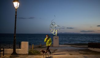 A man wearing a protective face mask walks with is dog in Alimos, a seaside suburb of Athens, on Tuesday, April 20, 2021. (AP Photo/Petros Giannakouris)
