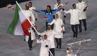 FILE - Samaneh Beyrami Baher carries the flag of Iran during the opening ceremony of the 2018 Winter Olympics in Pyeongchang, South Korea, in this Friday, Feb. 9, 2018, file photo. A group of athletes and human rights activists is calling on the IOC to sanction Iran's Olympic program for what it says is the country's long-running pattern of ordering athletes to avoid competing against Israelis in international events.  (AP Photo/Michael Sohn, File)