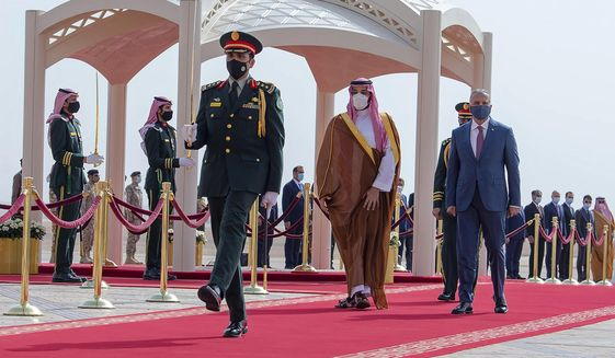 FILE - In this March 31, 2021 file photo, released by the Saudi Royal Palace, Saudi Crown Prince Mohammed bin Salman, center right, accompanies Iraqi Prime Minister Mustafa al-Kadhimi on his arrival to Riyadh International Airport, Saudi Arabia. A first round of direct talks held in April 2021, in Iraq, between regional rivals Saudi Arabia and Iran is seen as a positive sign of de-escalation following years of animosity. The hosting of the talks is also a significant step for Iraq, which has ties with both the U.S. and Iran and has often borne the brunt of Saudi-Iran rivalry. (Bandar Aljaloud/Saudi Royal Palace via AP, File)