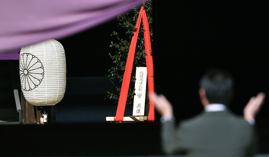"""A 'masakaki"""" tree offering, center, to Yasukuni Shrine by Japanese Prime Minister Yoshihide Suga, is placed as a man prays at the Shinto shrine in Tokyo Wednesday, April 21, 2021, the first day of the annual Spring Rites, the shrine's biannual festival honoring the war dead, including Japanese war criminals. Suga on Wednesday donated religions offerings to the shrine viewed by China and both Koreas as a symbol of wartime aggression, though he avoided a visit.The tree's plate reads: """"Prime Minister Yoshihide Suga."""" (Tsuyoshi Ueda/Kyodo News via AP)"""