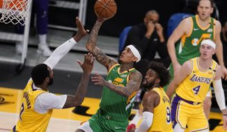 Utah Jazz guard Jordan Clarkson, center, shoots over Los Angeles Lakers center Andre Drummond, left, during the first half of an NBA basketball game Monday, April 19, 2021, in Los Angeles. (AP Photo/Marcio Jose Sanchez)