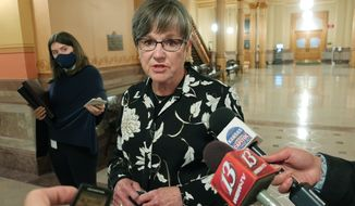 Kansas Gov. Laura Kelly speaks with reporters after vetoing a plan from Republican legislators for cutting state income taxes, Friday, April 16, 2021, at the Statehouse in Topeka, Kan. The measure would have saved taxpayers $284 million over three years, but the Democratic governor called it fiscally irresponsible. (AP Photo/John Hanna) **FILE**