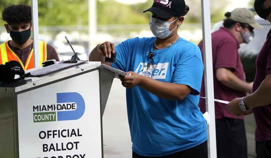 FILE - In this Oct. 26, 2020 file photo, an election worker stamps a vote-by-mail ballot dropped off by a voter before placing it in an official ballot drop box before at the Miami-Dade County Board of Elections in Doral, Fla. Democrats, voting rights advocates and the county officials responsible for running elections in Florida appeared powerless to halt moves by Republican lawmakers on Tuesday, April 20, 2021, to tighten the ways in which citizens can cast ballots.   (AP Photo/Lynne Sladky, File)