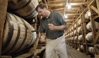 FILE – In this May 20, 2009, file photo, Jeff Arnett, the master distiller at the Jack Daniel Distillery in Lynchburg, Tenn., drills a hole in a barrel of whiskey in one of the aging houses at the distillery. The former top distiller at Jack Daniel's announced on Tuesday, April 20, 2021, that he and several partners are setting up shop for a new whiskey distillery near the Great Smoky Mountains in Tennessee. (AP Photo/Mark Humphrey, File)