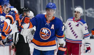 New York Islanders' Josh Bailey (12) celebrates with teammates after scoring a goal during the first period of an NHL hockey game against the New York Rangers on Tuesday, April 20, 2021, in Uniondale, N.Y. (AP Photo/Frank Franklin II)