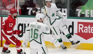 Detroit Red Wings defenseman Filip Hronek (17) skates past as Dallas Stars center Joe Pavelski (16) and left wing Jason Robertson (21) celebrate a goal scored by Robertson in the first period of an NHL hockey game in Dallas, Tuesday, April 20, 2021. (AP Photo/Tony Gutierrez)