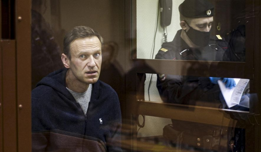 In this photo taken on Friday, Feb. 12, 2021 and provided by the Babuskinsky District Court, Russian opposition leader Alexei Navalny sits in a cage during a hearing on his charges for defamation in the Babuskinsky District Court in Moscow, Russia. A hunger strike by jailed Russian opposition leader Alexei Navalny cast a spotlight on the country's prison system that critics say is built on fear and torment. Navalny was transferred Sunday, April 18, 2021 from his prison colony to a hospital in another prison amid reports about his declining health that drew international outrage. Nearly 520,000 inmates occupy Russia's prison system - numerically by far the largest prison population in Europe. Most of the prisons are collective colonies, a system dating back to the Soviet Gulag era, with workshops and inmates sleeping in dormitories. (Babuskinsky District Court Press Service via AP, File)
