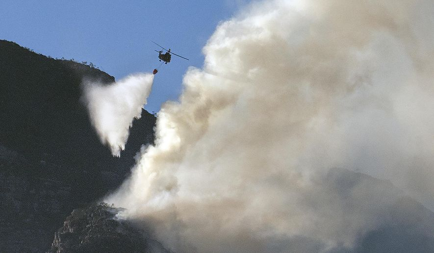 A South African military helicopter drops water on the top of Table Mountain in Cape Town, South Africa, Tuesday, April 20, 2021. A massive fire spreading on the slopes of the city's famed Table Mountain is kept under control as firemen and helicopters take advantage of the low winds to contain the blaze. (AP Photo/Jerome Delay)