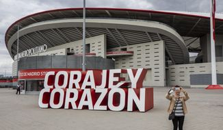 """A woman takes a snapshot in front Atletico Madrid's Wanda Metropolitano stadium in Madrid, Spain, Tuesday, April 20, 2021. A group of 12 elite English, Spanish and Italian clubs dramatically split European soccer on Sunday by announcing the formation of a largely-closed Super League. The Super League's founding chairman Florentino Perez on Tuesday, April 20, 2021 says the competition is being created to save soccer for everyone and not to make the rich clubs richer. The Real Madrid president says it's """"impossible"""" that players from the participating teams will be banned by UEFA. (AP Photo/Bernat Armangue) **FILE**"""