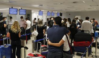 FILE - In this April 17, 2021, file photo, people check in for a flight to Miami at Silvio Pettirossi Airport, in Luque, Paraguay. Vaccine seekers who can afford to travel are coming to the United States to avoid the long wait, including people who have come from as far as Paraguay.  (AP Photo/Jorge Saenz, File)
