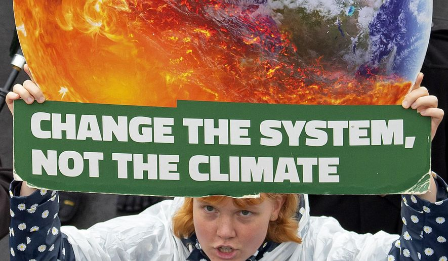 """A demonstrator holds a poster as she attends a protest climate strike and rally of the """"Friday For Future Movement"""" on Sept. 27, 2019. (Associated Press)"""