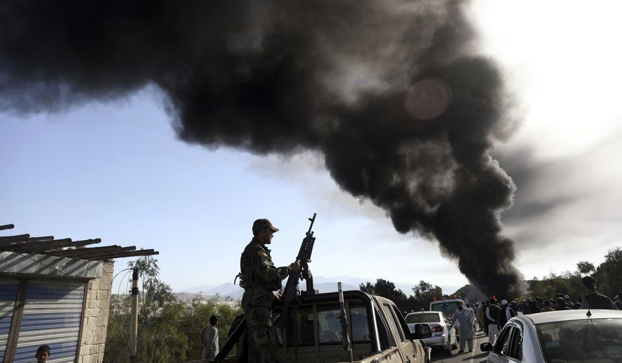 An Afghan army soldier stands guard as smoke rises from a burning fuel tanker after a road accident on the Jalalabad-Kabul highway, east of Kabul, Afghanistan, Wednesday, April 21, 2021. (AP Photo/Rahmat Gul) ** FILE **