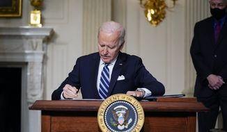 In this Jan. 27, 2021 file photo, President Joe Biden signs an executive order on climate change, in the State Dining Room of the White House in Washington. (AP Photo/Evan Vucci) ** FILE **