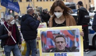 A demonstrator holds a picture of Russian jailed opposition leader Alexei Navalny during a protest organized by the Radical Party, in Rome, Wednesday, April 21, 2021. (AP Photo/Alessandra Tarantino) ** FILE **
