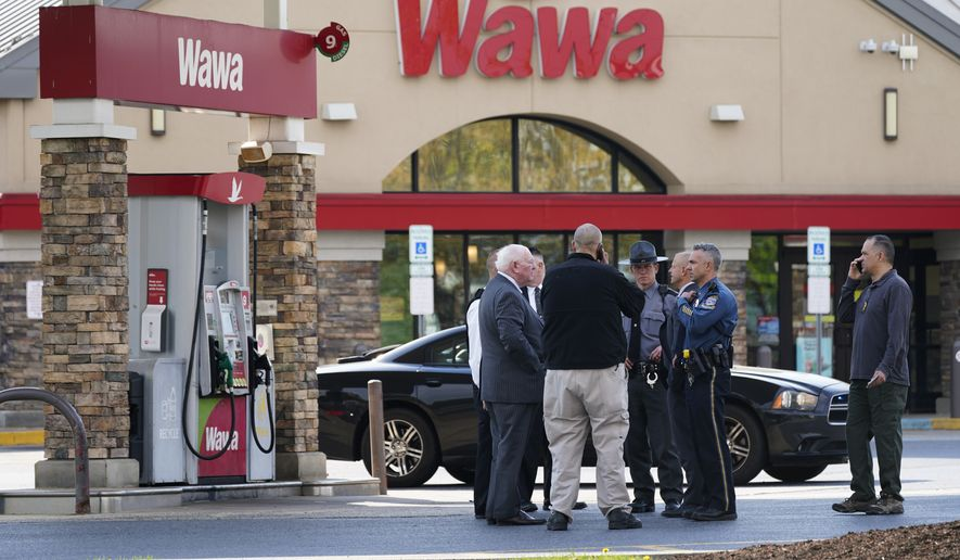 "Officials gather at a Wawa convenience store and gas station in Breinigsville, Pa., Wednesday, April 21, 2021. Police on Wednesday converged on the convenience store in eastern Pennsylvania following what state police called a ""serious police incident"" that has closed several businesses and a school. (AP Photo/Matt Rourke)"