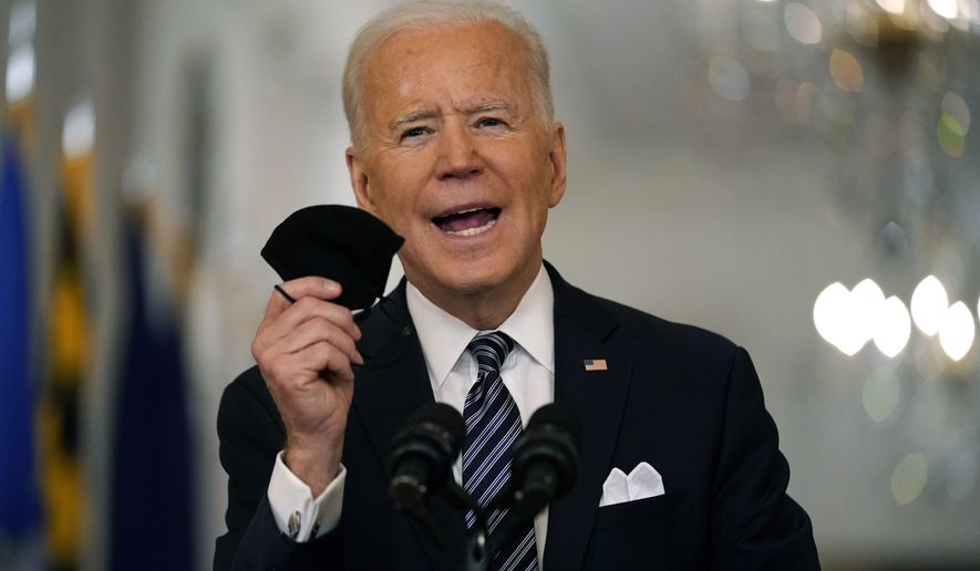 In this March 11, 2021, photo, President Joe Biden holds up his face mask as he speaks about the COVID-19 pandemic during a prime-time address from the East Room of the White House in Washington. The U.S. is meeting President Joe Biden's latest vaccine goal of administering 200 million COVID-19 shots in his first 100 days in office, as the White House steps up its efforts to inoculate the rest of the public.  (AP Photo/Andrew Harnik) **FILE**
