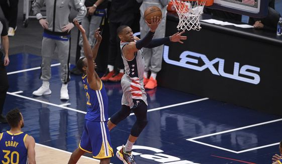 Washington Wizards guard Russell Westbrook (4) goes to the basket past Golden State Warriors forward Andrew Wiggins (22) and guard Stephen Curry (30) during the second half of an NBA basketball game, Wednesday, April 21, 2021, in Washington. The Wizards won 118-114. (AP Photo/Nick Wass)