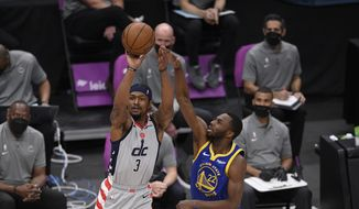 Washington Wizards guard Bradley Beal (3) shoots next to Golden State Warriors forward Andrew Wiggins (22) during the first half of an NBA basketball game, Wednesday, April 21, 2021, in Washington. (AP Photo/Nick Wass)