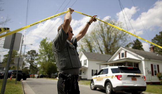 Law enforcement investigate the scene of a shooting, Wednesday, April 21, 2021, in Elizabeth City, N.C. At least one law enforcement officer with a sheriff's department in North Carolina shot and killed a man while executing a search warrant Wednesday, the sheriff's office said. (Stephen M. Katz/The Virginian-Pilot via AP)