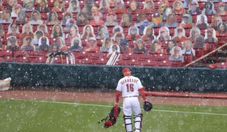 Cincinnati Reds' Tucker Barnhart walks to the bullpen as snow falls prior to the continuation of a baseball game against the Arizona Diamondbacks in Cincinnati, Wednesday, April 21, 2021. The game was suspended in the eighth inning the day before due to rain. (AP Photo/Aaron Doster)