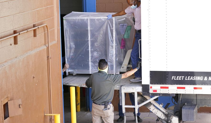 Officials unload election equipment into the Veterans Memorial Coliseum at the state fairgrounds, Wednesday, April 21, 2021, in Phoenix. Maricopa County officials began delivering equipment used in the November election won by President Joe Biden on Wednesday and will move 2.1 million ballots to the site Thursday so Republicans in the state Senate who have expressed uncertainty that Biden's victory was legitimate can recount them and audit the results. (AP Photo/Matt York)