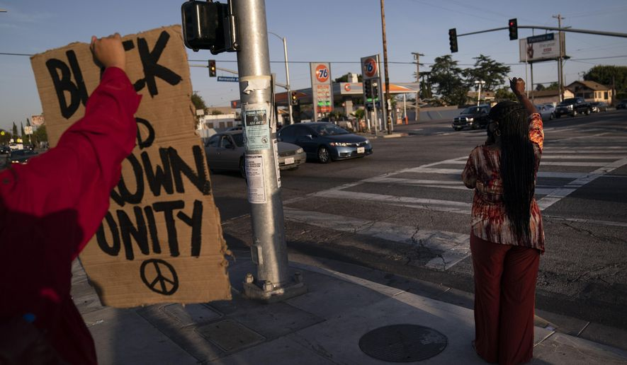 Joyce Robertson, right, clenches her fist at the intersection of Florence and Normandie Avenues in Los Angeles, Tuesday, April 20, 2021, after a guilty verdict was announced at the trial of former Minneapolis police Officer Derek Chauvin for the 2020 death of George Floyd. (AP Photo/Jae C. Hong)