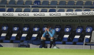 Arena: Schalke defender Timo Becker sits alone on the bench after the German Bundesliga soccer match at Schueco Arena in Bielefeld, Germany, Tuesday April 20, 2021. (Friso Gentsch/pool via AP)