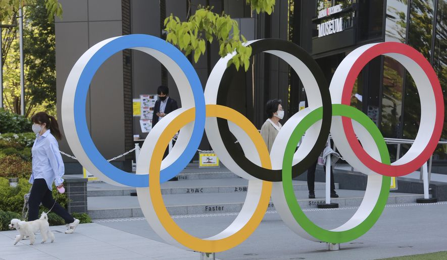A woman with her dog walks past the Olympic rings in Tokyo, Tuesday, April 20, 2021. (AP Photo/Koji Sasahara) **FILE**
