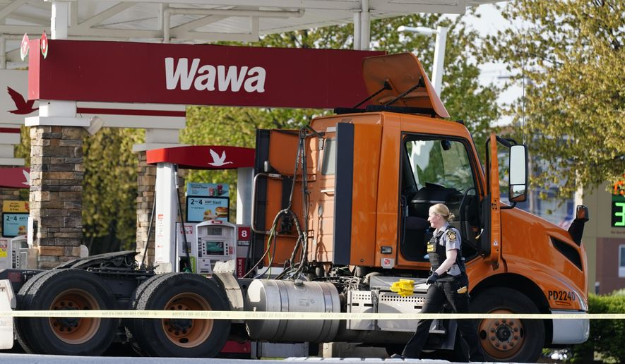 """An investigator works the crime scene at a Wawa convenience store and gas station in Breinigsville, Pa., Wednesday, April 21, 2021. Police on Wednesday converged on a convenience store in eastern Pennsylvania following what state police called a """"serious police incident"""" that has closed several businesses and a school. (AP Photo/Matt Rourke)"""