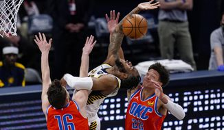 Indiana Pacers forward Oshae Brissett (12) is fouled by Oklahoma City Thunder guard Ty Jerome (16) on a shot during the first half of an NBA basketball game in Indianapolis, Wednesday, April 21, 2021. (AP Photo/Michael Conroy)