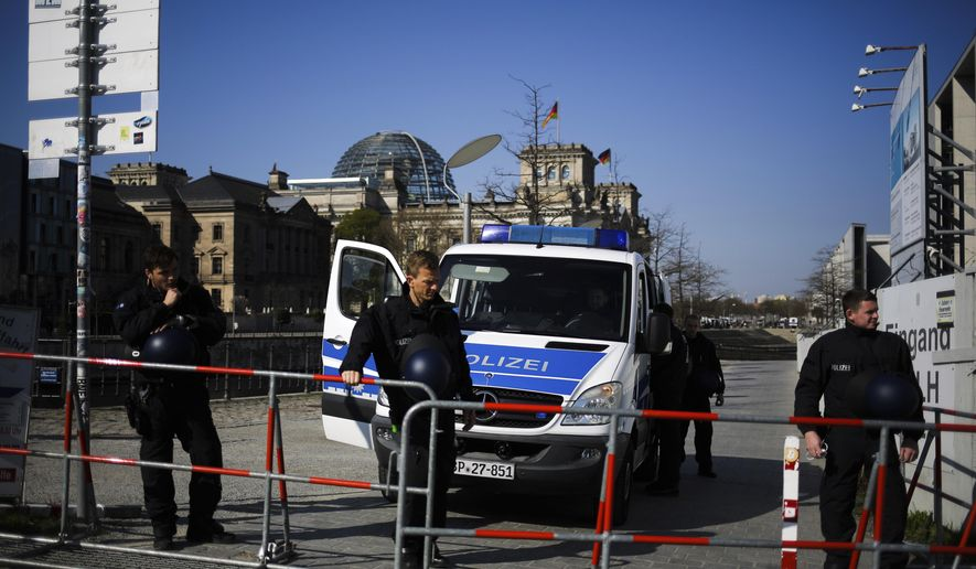 Police officers secure the German parliament, the Reichstag building prior to a protest rally against the government's policy to battle the corona virus pandemic in Berlin, Germany, Wednesday, April 21, 2021. The parliament decides on a law that gives the federal government more power to battle the coronavirus pandemic. (AP Photo/Markus Schreiber)