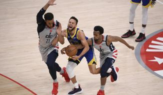 Washington Wizards center Daniel Gafford (21) and guard Ish Smith right, battle for the ball against Golden State Warriors guard Stephen Curry, center, during the second half of an NBA basketball game, Wednesday, April 21, 2021, in Washington. Gafford was called for a foul on the play. (AP Photo/Nick Wass)