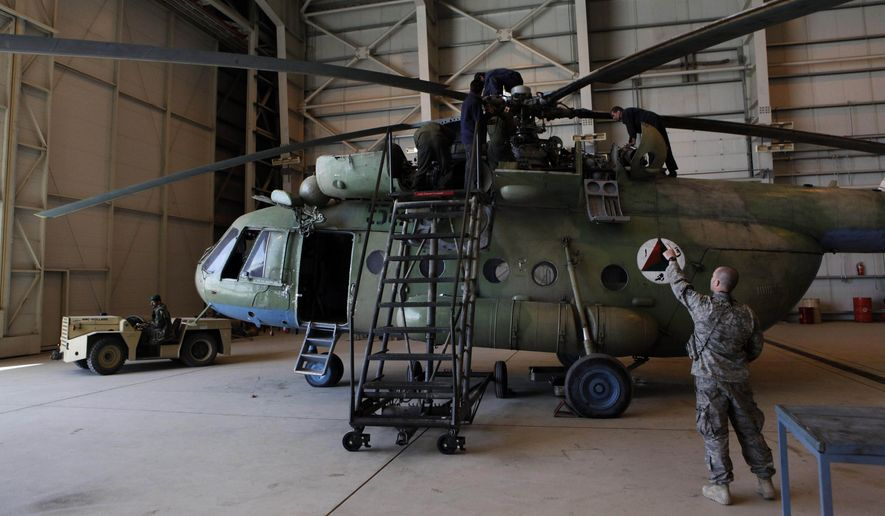In this April 6, 2010 file photo, Sgt. Troy Bencke, right, points toward Afghan air force engineers as they work on an Mi-17 helicopter inside a hangar in Kabul, Afghanistan.  (AP Photo/Dar Yasin)