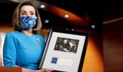 House Speaker Nancy Pelosi of Calif., holds up a photograph of her father, Thomas D'Alesandro Jr., with Eleanor Roosevelt, as she speaks about the long fight for DC statehood during her weekly press briefing on Capitol Hill, Thursday, April 22, 2021, in Washington. (AP Photo/Andrew Harnik)