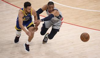 Washington Wizards guard Russell Westbrook (4) and Golden State Warriors guard Stephen Curry (30) chase a loose ball during the first half of an NBA basketball game, Wednesday, April 21, 2021, in Washington. (AP Photo/Nick Wass)
