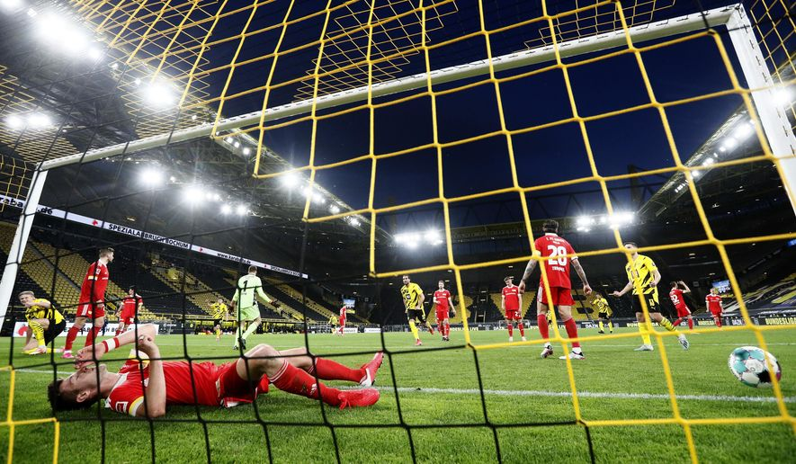 Union's Robin Knoche reacts as Dortmund's Marco Reus, left, celebrates scoring his side's first goal during the German Bundesliga soccer match between Borussia Dortmund and Union Berlin in Dortmund, Germany, Wednesday, April 21, 2021.(AP Photo/Martin Meissner, pool)