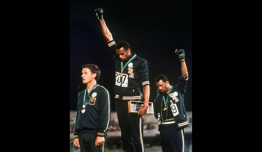 """In this Oct. 16, 1968 file photo, U.S. athletes Tommie Smith, center, and John Carlos raise their gloved fists after Smith received the gold and Carlos the bronze for the 200 meter run at the Summer Olympic Games in Mexico City. Athletes who make political or social justice protest at the Tokyo Olympics were promised legal support Thursday April 22, 2021, by a global union and an activist group in Germany. The pledges came one day after the International Olympic Committee confirmed its long-standing ban on """"demonstration or political, religious or racial propaganda"""" on the field of play, medal podiums or official ceremonies. (AP Photo/File) **FILE**"""