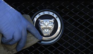 FILE - In this Wednesday Sept. 28, 2016 file photo, a worker polishes a Jaguar logo on a car at a Jaguar dealer in London. Jaguar Land Rover said Thursday April 22, 2021, it's suspending production at two U.K. factories, becoming the latest automaker to fall victim to a global shortage of microchips. (AP Photo/Frank Austin, file)