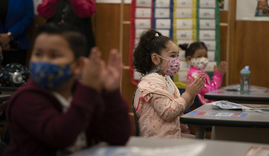 In this April 13, 2021, file photo, first graders applaud while listening to their teacher in a classroom on the first day of in-person learning at Heliotrope Avenue Elementary School in Maywood, Calif. (AP Photo/Jae C. Hong, File)