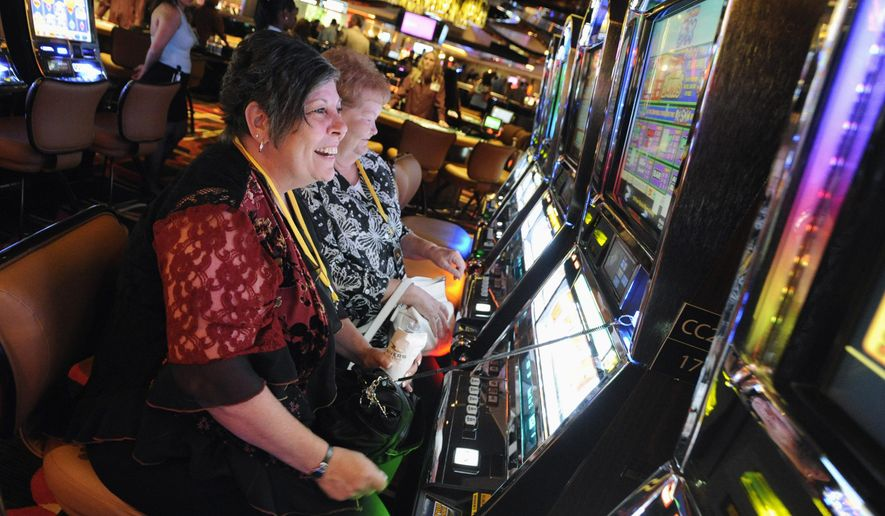 """FILE - In this July 15, 2011 file photo, Karen Lingermuth, of Niles, Ill., plays the slots during a special VIP event at the Rivers Casino in the Chicago suburb of Des Plaines, Ill. Chicago is taking a big step toward building its long-awaited first casino. Starting Thursday, April 22, 2021, city officials are officially seeking bids from companies interested in what's being billed as a """"world-class"""" resort scheduled to open by 2025. (Mark Welsh/Daily Herald via AP, File)"""
