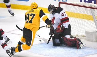 New Jersey Devils goaltender Aaron Dell (47) blocks a shot by Pittsburgh Penguins' Sidney Crosby (87) during the first period of an NHL hockey game in Pittsburgh, Thursday, April 22, 2021. (AP Photo/Gene J. Puskar)