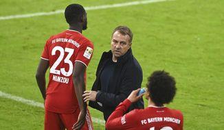 Bayern's head coach Hans-Dieter Flick speaks to Bayern's Leroy Sane during the German Bundesliga soccer match between Bayern Munich and Bayer Leverkusen at the Allianz Arena stadium in Munich, Germany, Tuesday, April 20, 2021. (Christof Stache, Pool via AP)