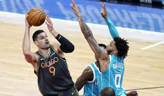 Chicago Bulls' Nikola Vucevic (9) shoots over Charlotte Hornets' Miles Bridges during the first half of an NBA basketball game Thursday, April 22, 2021, in Chicago. (AP Photo/Charles Rex Arbogast)