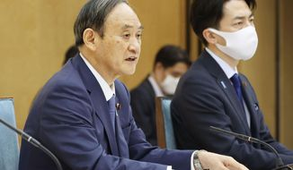Japanese Prime Minister Yoshihide Suga, left, and Minister of the Environment Shinjiro Koizumi attend the global warming meeting at the prime minister's office in Tokyo, Thursday, April 22, 2021.  Japan said Thursday it will raise its greenhouse gas emissions reduction target to 46% on 2013 levels from 26%, NHK television reported. Prime Minister Suga has set a goal to achieve carbon neutrality in Japan by 2050.(Kyodo News via AP)