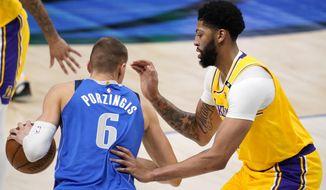 Dallas Mavericks' Kristaps Porzingis (6) works to the basket against Los Angeles Lakers forward Anthony Davis during the first half of an NBA basketball game in Dallas, Thursday, April 22, 2021. (AP Photo/Tony Gutierrez)