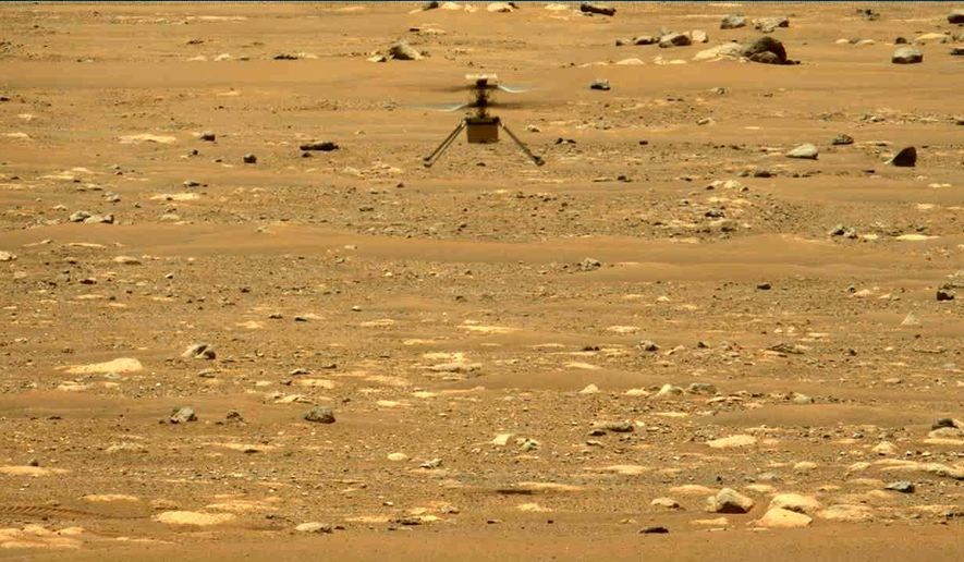 In this image made available by NASA, the Mars Ingenuity helicopter hovers above the surface of the planet during its second flight on Thursday, April 22, 2021. (NASA/JPL-Caltech/ASU/MSSS via AP)