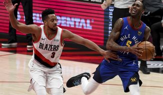 Portland Trail Blazers guard CJ McCollum, left, fouls Denver Nuggets forward Will Barton during the first half of an NBA basketball game in Portland, Ore., Wednesday, April 21, 2021. (AP Photo/Steve Dykes)