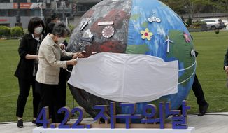 Participants release a mask from an earth-shaped balloon as they perform a skit against climate change during the Earth Day ceremony in Seoul, South Korea, Thursday, April 22, 2021. (AP Photo/Lee Jin-man)