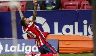 Atletico Madrid's Angel Correa celebrartes after scoring his side's first goal during the Spanish La Liga soccer match between Atletico Madrid and Huesca at the Wanda Metropolitano stadium in Madrid, Spain, Thursday, April 22, 2021. (AP Photo/Manu Fernandez)
